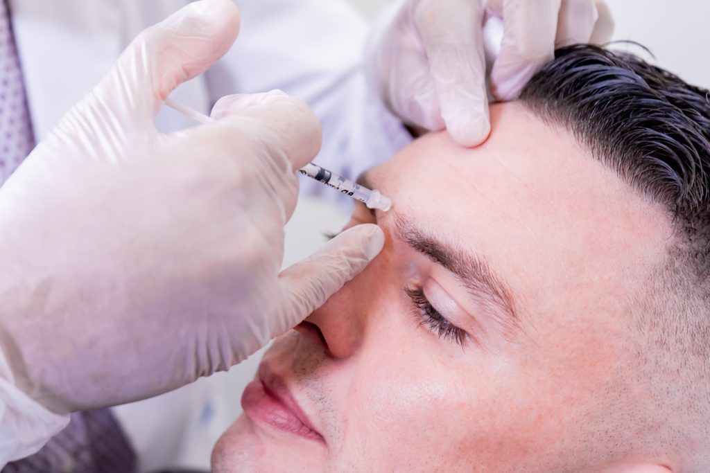 Caucasian man undergoing beauty spa botulinum neurotoxin Botox treatment for anti-aging, to smooth wrinkles as a cometic solution. Injecting forehead to relax muscles with a non-invasive procedure.Caucasian man undergoing beauty spa botulinum neurotoxin Botox treatment for anti-aging, to smooth wrinkles as a cometic solution. Injecting forehead to relax muscles with a non-invasive procedure.